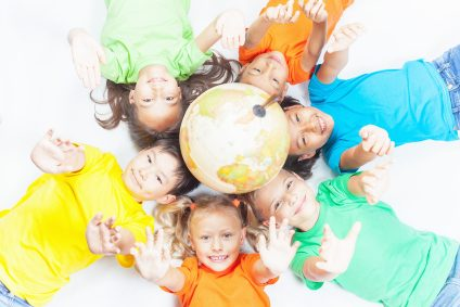 Group of international funny kids. Lying with globe earth, looking up at camera. Smiling. School children learn geography. Multi Ethnic people. World. Ecology. Pure earth. International Children's Day