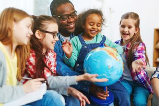 Teacher with his pupils studying the world with the help of globe